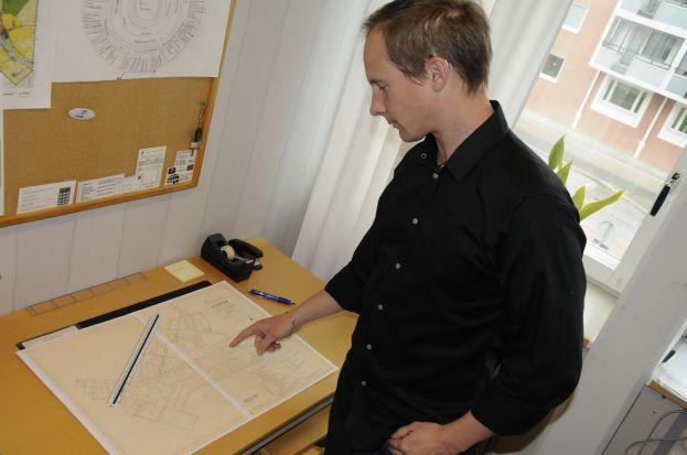 Stadsplaneraren Erik Isaksson visar upp den gamla detaljplanen för Vistträsk. Foto: Robin Nilsson.