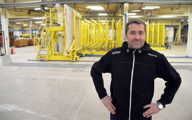Stefan Johansson, bygg- och produktionschef, framför slutdelen av den nya vägglinjen (den gula konstruktionen). I facken levereras de färdiga väggelementen för att sedan med travers tas till monteringen. Foto: Tony Berglund