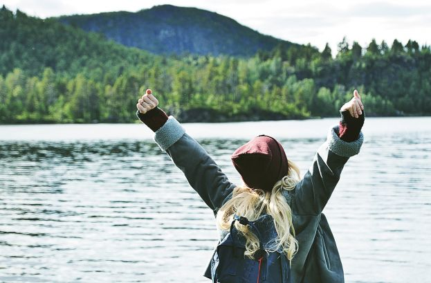 Skolelev sträcker ut armarna mot himlen. I bakgrunden syns vatten, skog och berg.